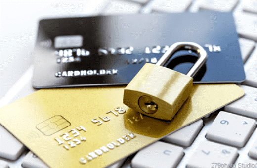 Padlock on top of credit cards on computer keyboard